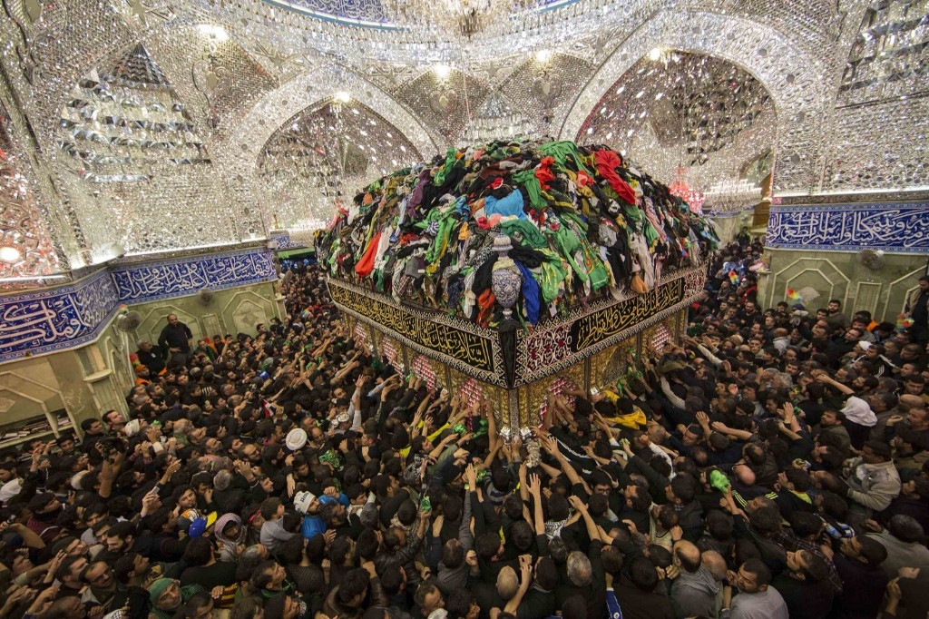 Shi'ite Muslim pilgrims reach out to touch the tomb of Imam al-Abbas to mark Arbain in the holy city of Kerbala, southwest of Baghdad. REUTERS/Stringer