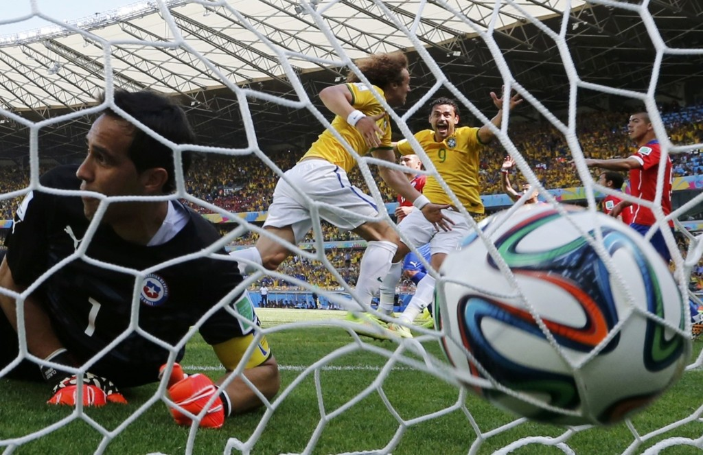 Brazil's David Luiz scoring a goal against Chile's goalkeeper Claudio Bravo. REUTERS/Sergio Perez