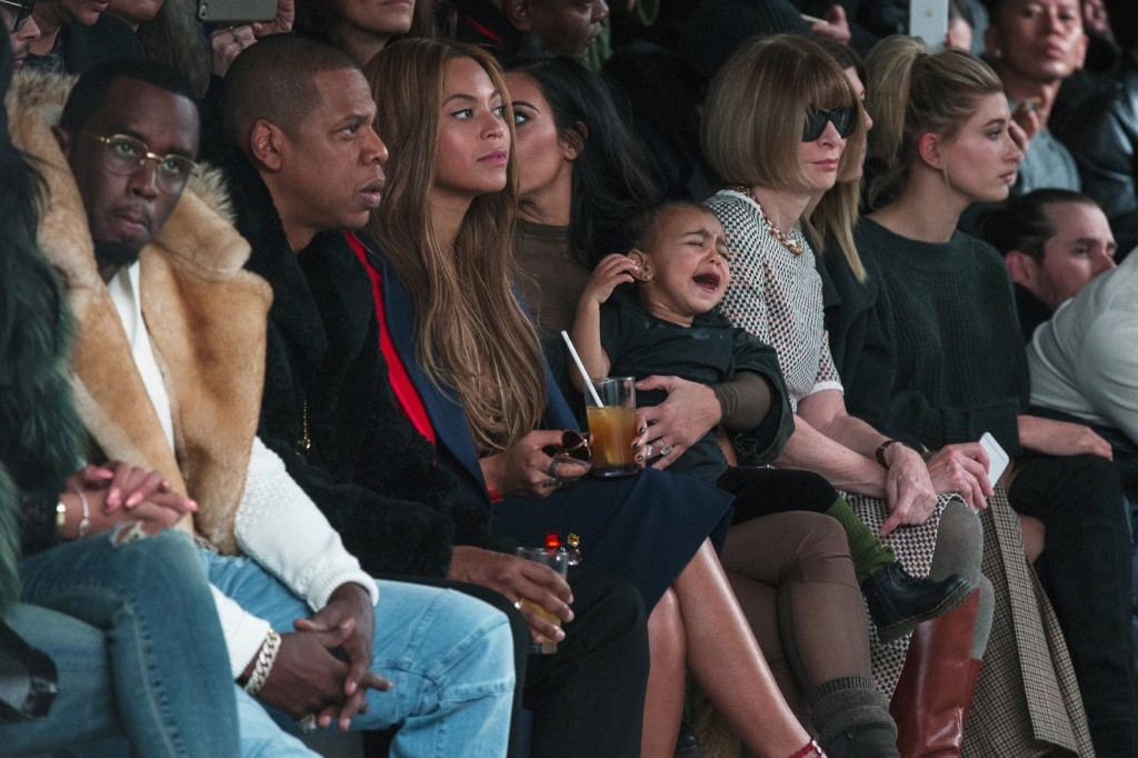 Kim Kardashian attempts to calm her daughter, North, while sitting next to Sean Combs, Jay-Z, Beyonce and Anna Wintour as they watch a presentation of Kanye West's Fall/Winter 2015 partnership with Adidas at New York Fashion Week, Thursday. REUTERS/Lucas Jackson