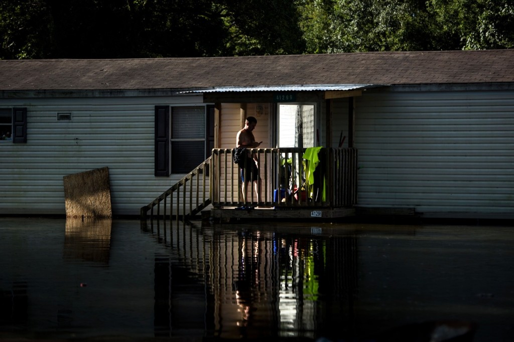 A man stands on the stairs of a home surrounded by flood waters in Gonzales, La. BRENDAN SMIALOWSKI/AFP/Getty Images