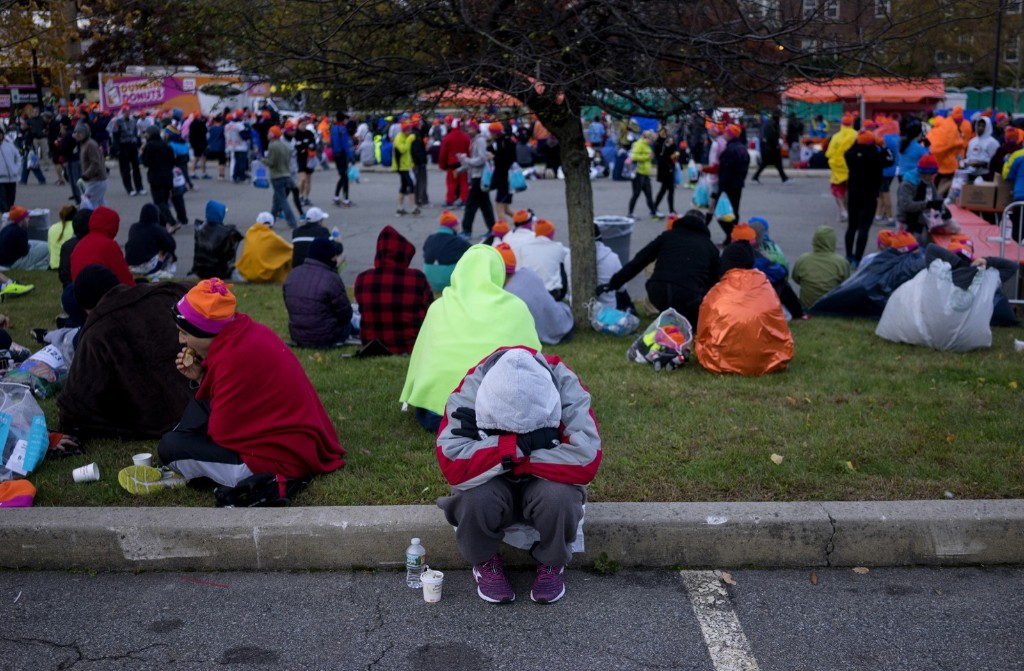 A runner huddles from the wind and cold before the start of the race. AP Photo/Craig Ruttle