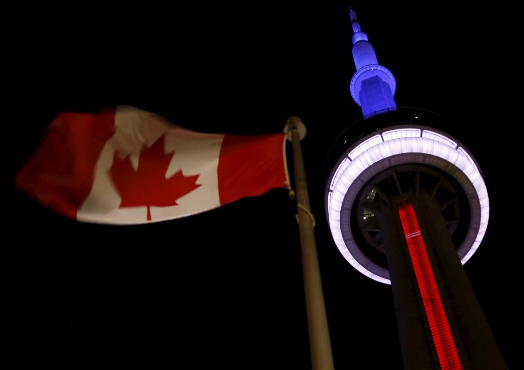 The landmark CN Tower in Toronto is lit blue, white and red in the colors of the French flag. REUTERS/Chris Helgren