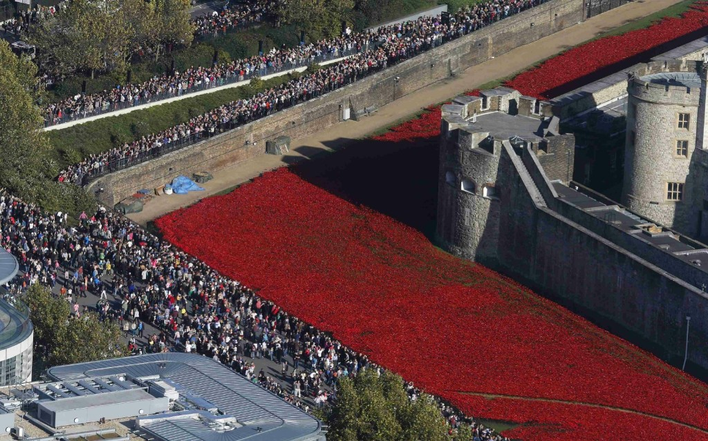 "Crowds gather to see the red ceramic poppies that form part of the art installation ""Blood Swept Lands and Seas of Red"" at the Tower of London. REUTERS/Suzanne Plunkett"