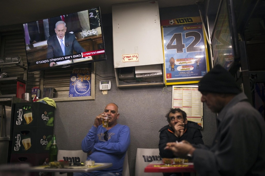 People sit under a television broadcasting Israel's Prime Minister Benjamin Netanyahu's speech to the U.S. Congress, at a kiosk in the southern city of Ashkelon in Israel, Tuesday. REUTERS/Amir Cohen
