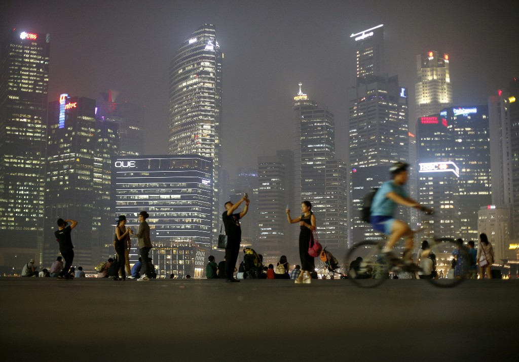 FILE PHOTO: People take photos with the skyline of the central business district in Singapore September 10, 2015. REUTERS/Edgar Su/File Photo