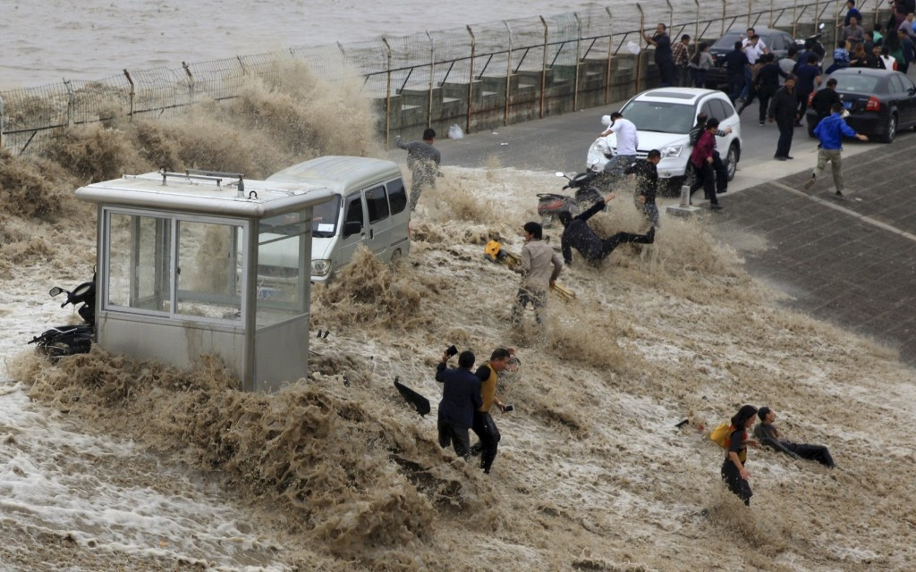 Visitors are hit by a wave caused by a tidal bore which surged past a barrier on the banks of Qiantang River, in Hangzhou, China. REUTERS/China Daily