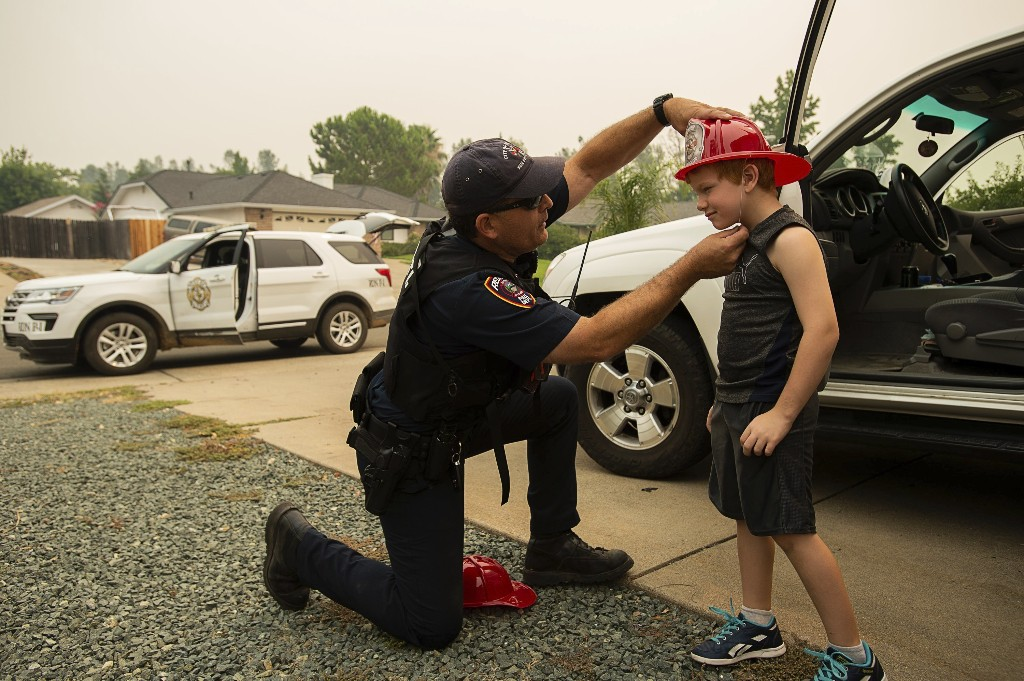 Fire Marshall Craig Wittner adjusts a plastic fire hat to returning resident Cayden Campbell, 6, during the Carr Fire on Monday, July 30, 2018, in Redding, Calif. Some evacuations orders have been lifted around a Northern California wildfire area near the city of Redding. The California Department of Forestry and Fire Protection said people can return to several neighborhoods in western Redding as of Monday morning. (Paul Kitagaki Jr./The Sacramento Bee via AP)