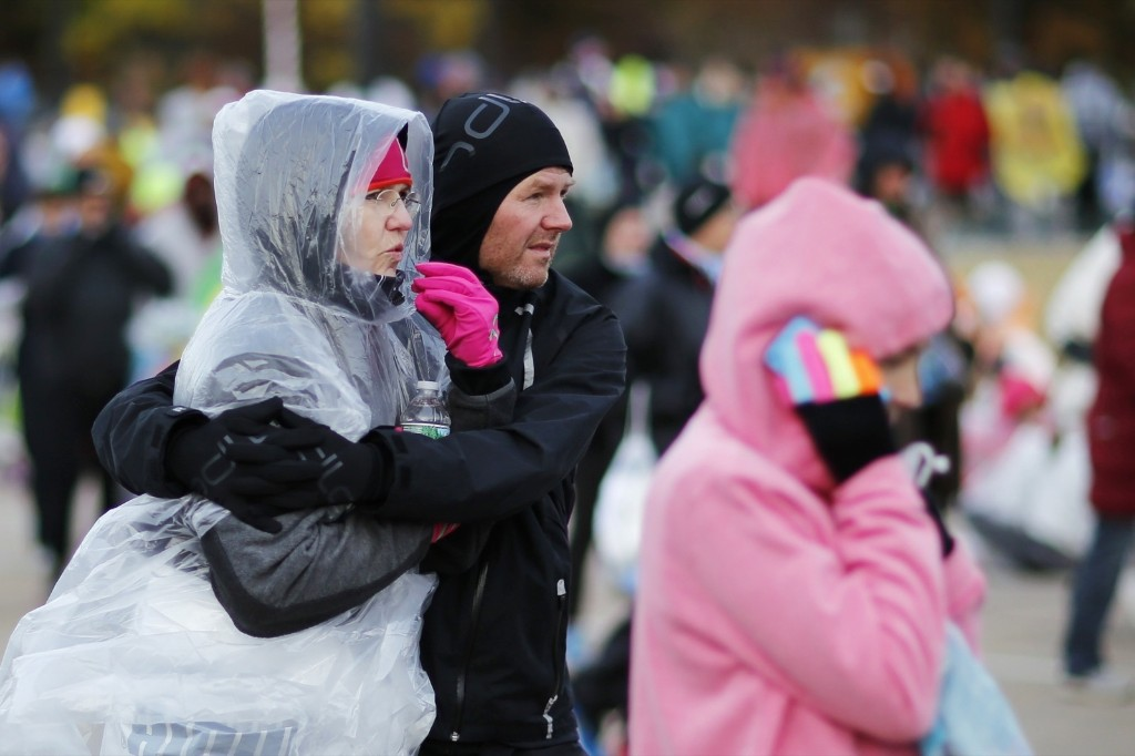 Runners take cover from the unusually cold morning. REUTERS/Eduardo Munoz