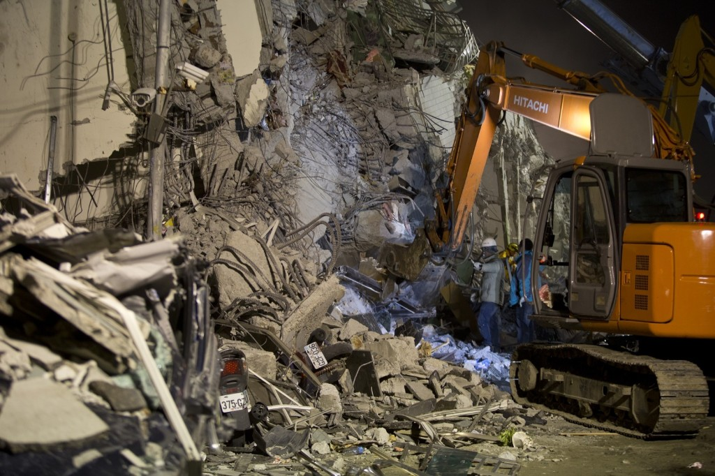 Rescue personnel search for survivors at the site of a collapsed building. Ashley Pon/Getty Images