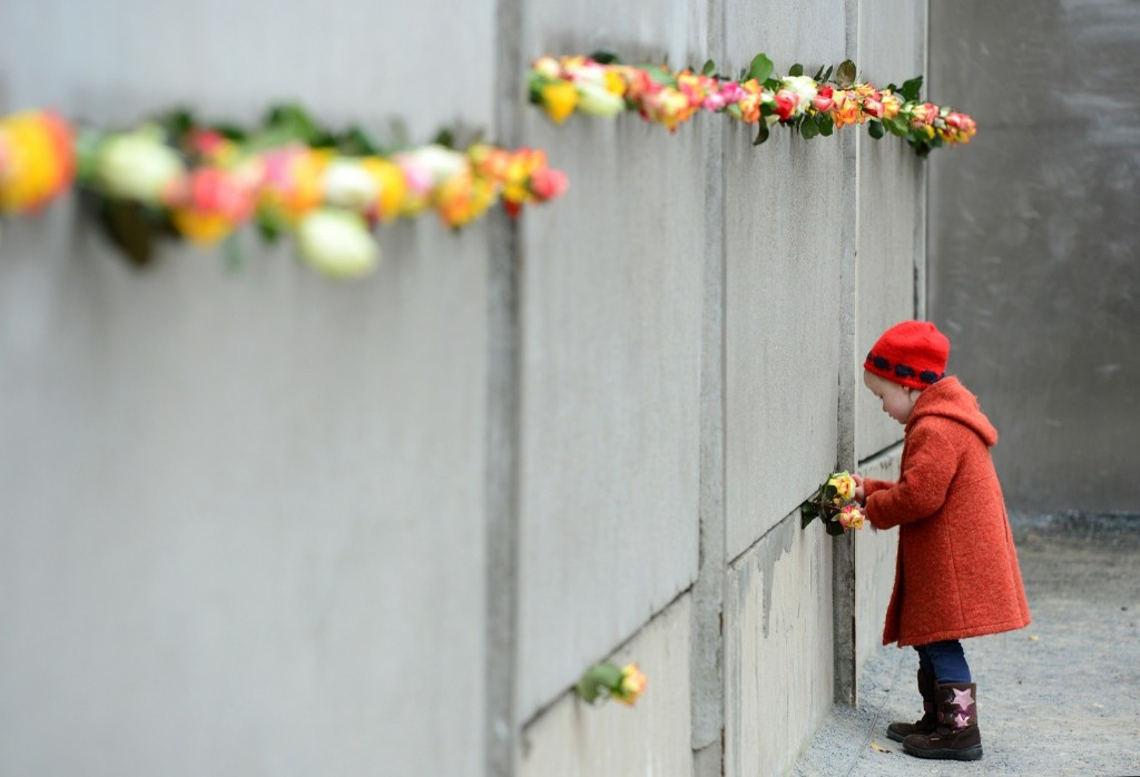 A young girl slips a rose in a preserved segment of the Berlin Wall during commemorations to mark the 25th anniversary of its fall. JOHN MACDOUGALL/AFP/Getty Images
