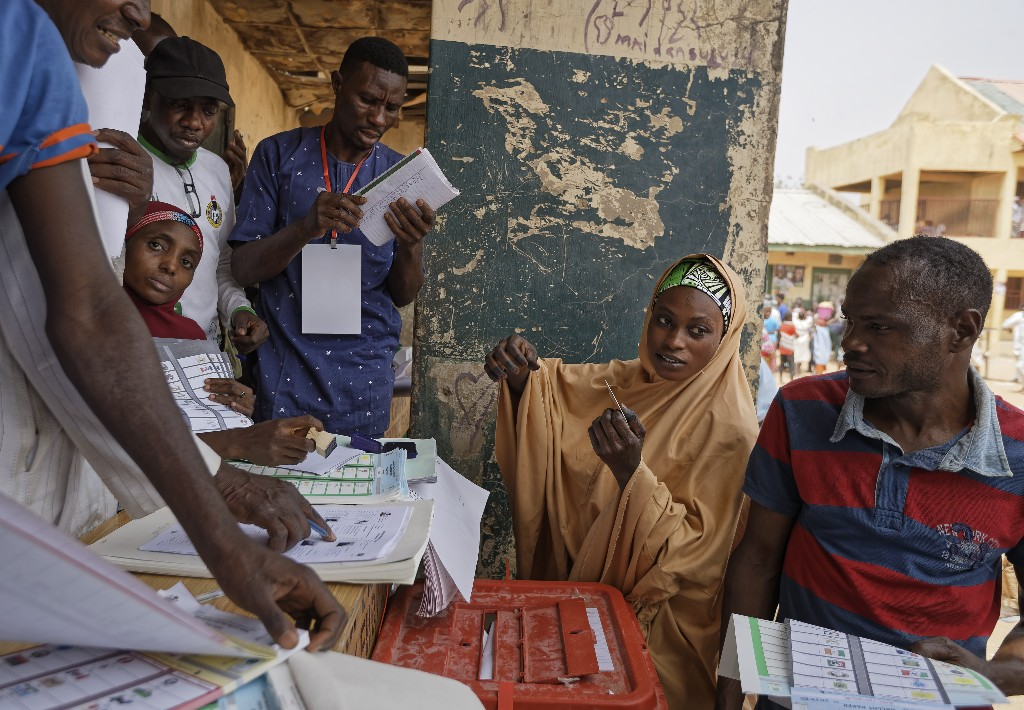 A woman voter verifies her voter registration before casting her vote at a polling station in Kano, northern Nigeria Saturday, Feb. 23, 2019. Nigerians are going to the polls for a presidential election Saturday, one week after a surprise delay for Africa's largest democracy. (AP Photo/Ben Curtis)