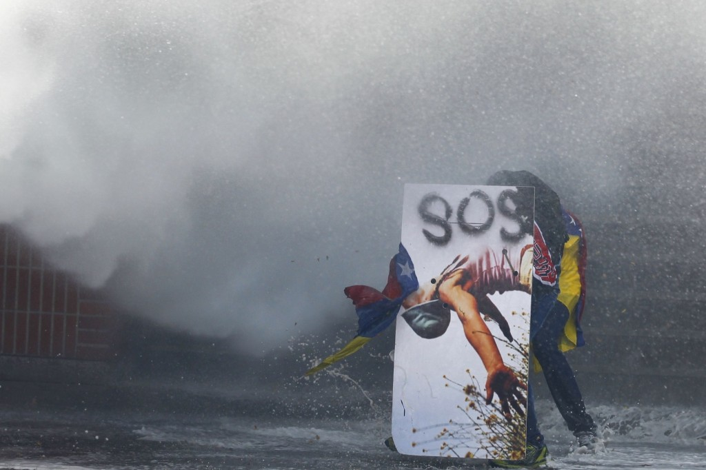 An anti-government protester takes cover behind a makeshift shield in Caracas. REUTERS/Carlos Garcia Rawlins