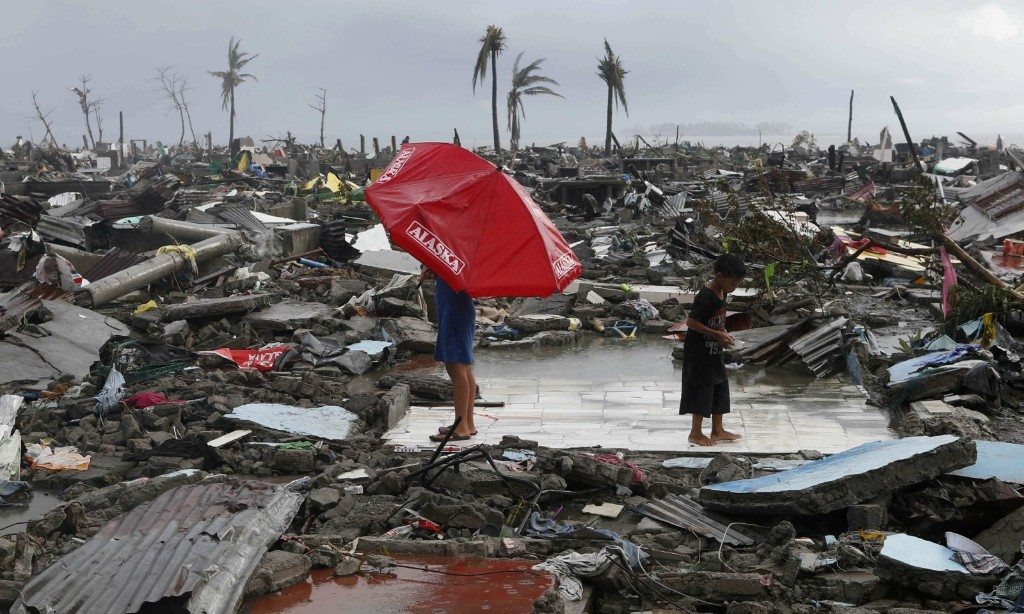 Residents stand on the ruins of their house. REUTERS/Erik De Castro