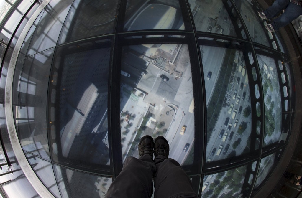 A person stands on the SkyPortal, a 14-foot wide disc that delivers high-definition live video footage from the street below, in the One World Observatory on the 100th floor of the One World Trade Center tower in New York, Wednesday. REUTERS/Mike Segar