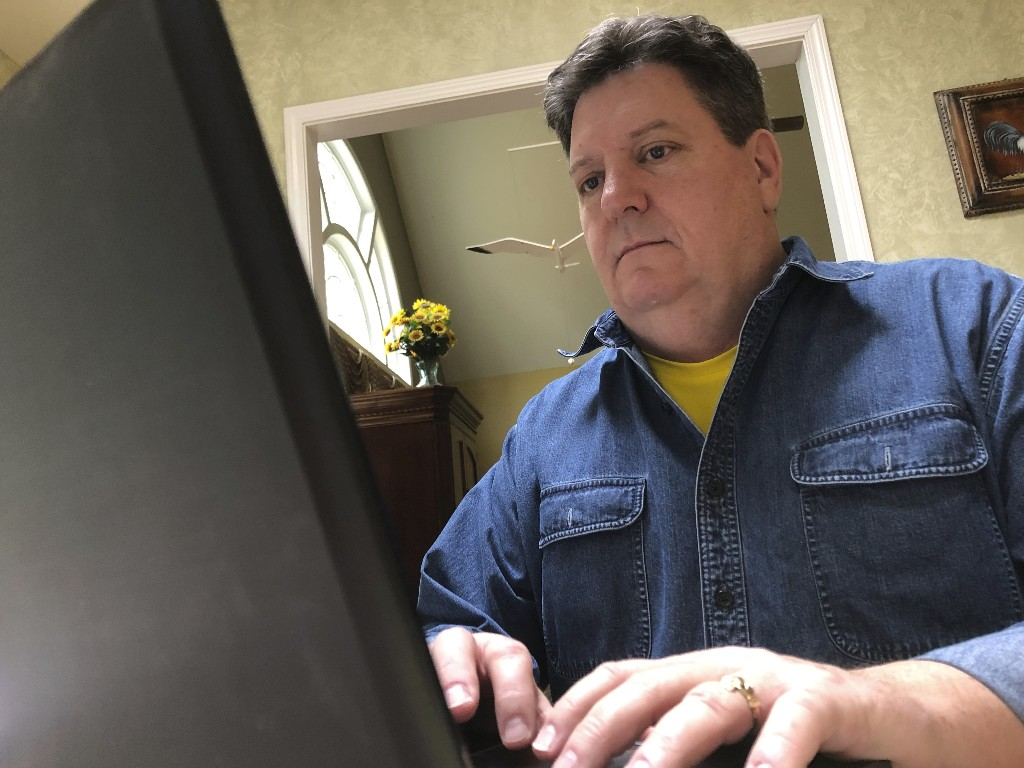 In this Friday, Feb. 15, 2019, photo Kevin McCreanor works on a laptop in Atlanta. The first tax filing season under the new federal tax law is proving to be surprising, confusing (and occasionally frightening) for some Americans. McCreanor and his wife normally get a sizeable refund each year. While they know waiting for a large refund isn't the best strategy financially, they like a refund and they put anything they get back toward their daughters' education. Their income, earned primarily from his wife's job in telecom, can vary greatly, so there was comfort in never facing a big bill. (AP Photo/Cody Jackson)