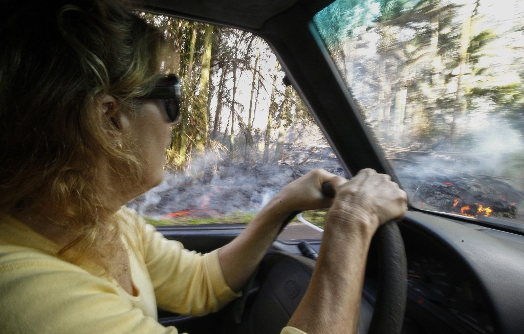 In this Sunday, May 6, 2018, photo, Leilani Estates resident Lucina Aquilina drives near lava on Luana Street in the Leilani Estates subdivision, in Pahoa, Hawaii. Hawaii's Kilauea volcano has destroyed homes and spewed lava hundreds of feet into the air, leaving evacuated residents unsure how long they might be displaced. (Jamm Aquino/Honolulu Star-Advertiser via AP)