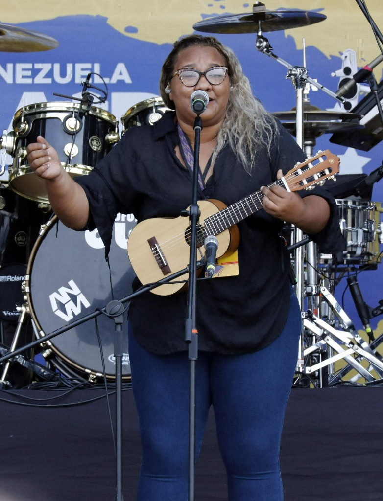 "Reymar Perdomo sings ""I Left,"" during the Venezuela Aid Live concert on the Colombian side of the Tienditas International Bridge near Cucuta, Colombia, on the border with Venezuela, Friday, Feb. 22, 2019. Her song has become the unofficial anthem of Venezuelans fleeing their country's economic and political crisis. (AP Photo/Fernando Vergara)"