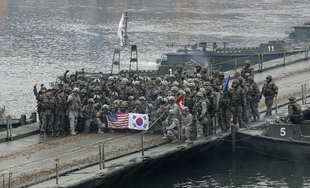 FILE - In this Dec. 10, 2015, file photo, U.S. and South Korean army soldiers pose on a floating bridge on the Hantan river after a river crossing operation, part of an annual joint military exercise between South Korea and the United States in Yeoncheon, south of the demilitarized zone that divides the two Koreas, South Korea. Ahead of the second summit between U.S. President Donald Trump and North Korean leader Kim Jong Un, some observers say there is an uncertainty over the future of the decades-long military alliance between Washington and Seoul. (AP Photo/Ahn Young-joon, File)