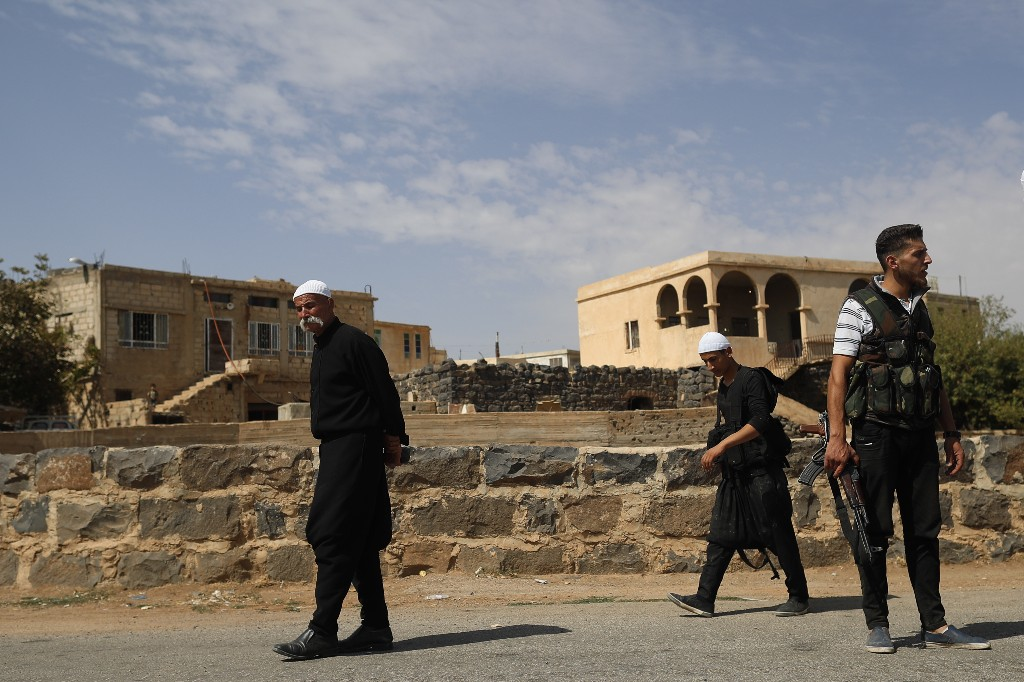 FILE - In this Thursday, Oct. 4, 2018, file photo, young Druze armed men, who carry weapons to defend their village from Islamic State attack, patrol the village of Rami in the southern province of Sweida, Syria. Syrian troops have liberated 19 women and children hostages held by the Islamic State group since July in a military operation in the country's center, ending a crisis that has stunned Syria's Druze minority, state media reported Thursday, Nov. 8, 2018. (AP Photo/Hassan Ammar, File)
