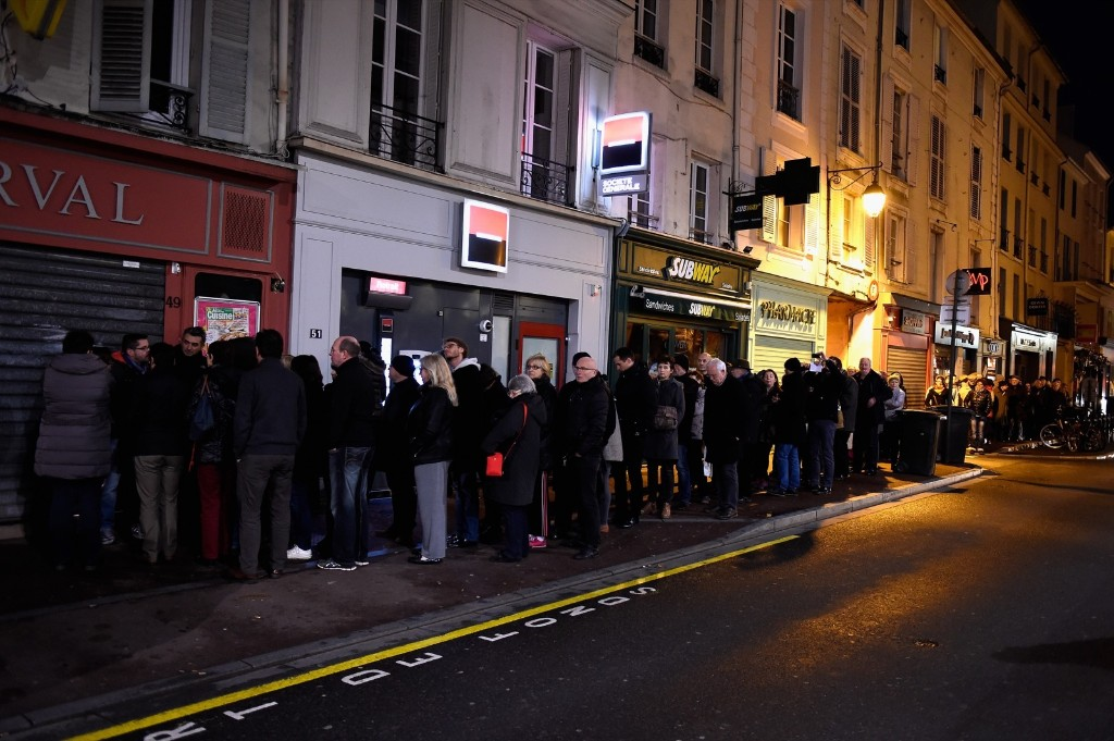 People wait outside a kiosk to buy a copy of Charlie Hebdo, Wednesday in Saint Germain en Laye, France. Pascal Le Segretain/Getty Images