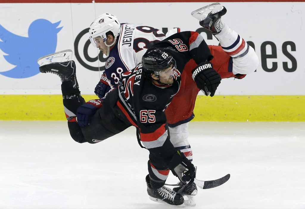Carolina Hurricanes Ron Hainsey (65) and Columbus Blue Jackets Boone Jenner collide during game in Raleigh, N.C., AP Photo/Gerry Broome