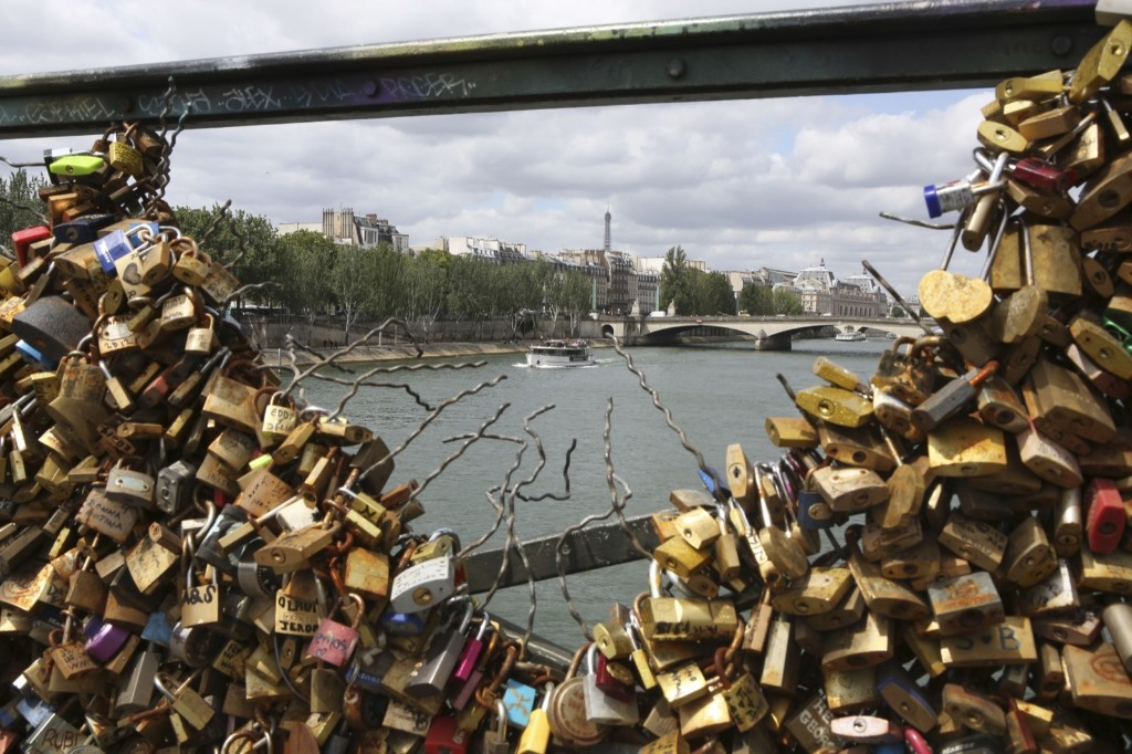 The Eiffel Tower appears through the partly lock-free railing of the famed Pont des Arts bridge in Paris, Monday. AP Photo/Remy de la Mauviniere