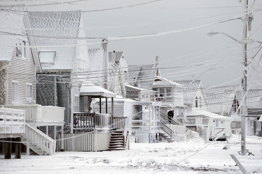 Dexter Newcomb begins cleanup at his house in Scituate, Mass., the day after a winter storm left his neighborhood coated in frozen sea spray and sand. AP Photo/Michael Dwyer