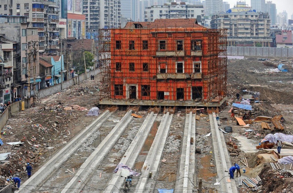 Workers prepare to move an historic site on Changdi Street in Wuhan, Hubei Province of China. The building was used as a volunteer fire headquarters in the early Republic of China. It will move 90 meters to the east on concrete rails so the original location can be redeveloped. ChinaFotoPress via Getty Images