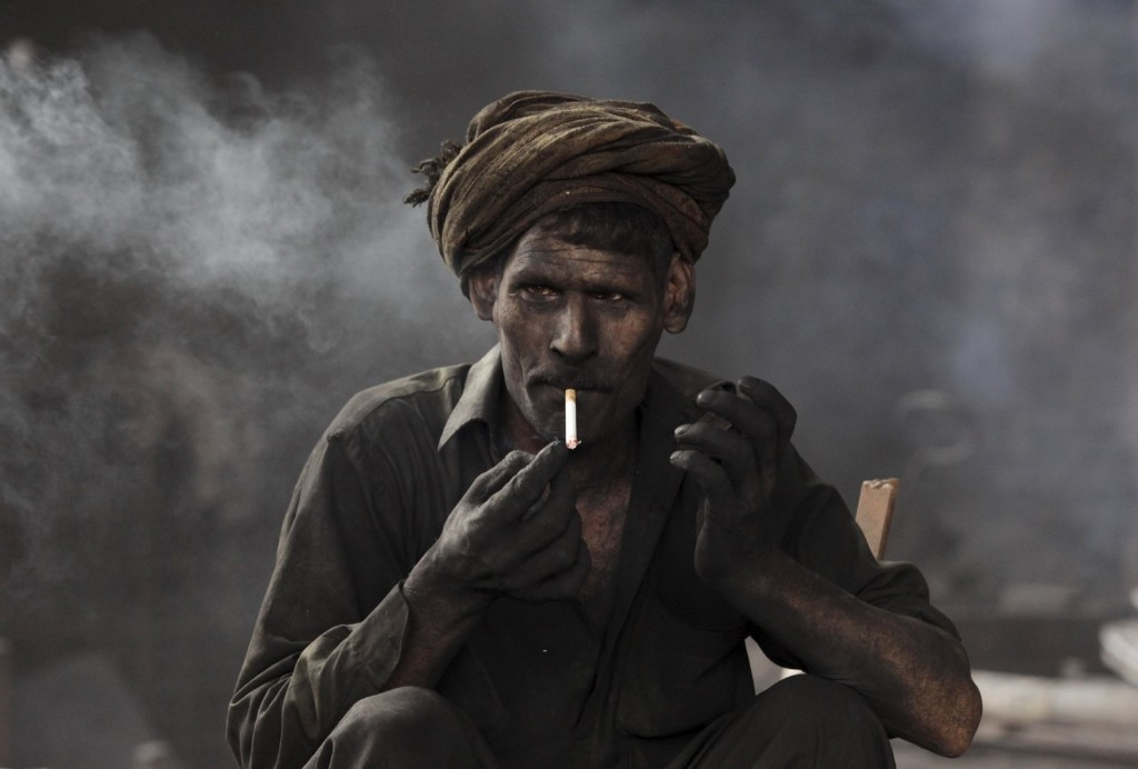 A worker takes a break at a steel smelting plant in Lahore. REUTERS/Mohsin Raza