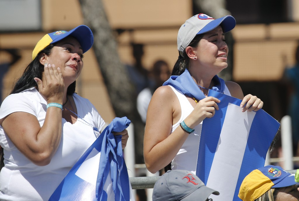 Two women cry during an event to swear in nurses, doctors, professionals and others, as the group that will help with the arrival and distribution of humanitarian aid in Venezuela, during and event in Caracas, Venezuela, Saturday, Feb. 16, 2019. The U.S. Air Force has begun flying tons of aid to a Colombian town on the Venezuelan border as part of an effort meant to undermine socialist President Nicolas Maduro. The first of three C-17 cargo planes has flown from Homestead Air Reserve Base in Florida and landed in the town of Cucuta.(AP Photo/Ariana Cubillos)