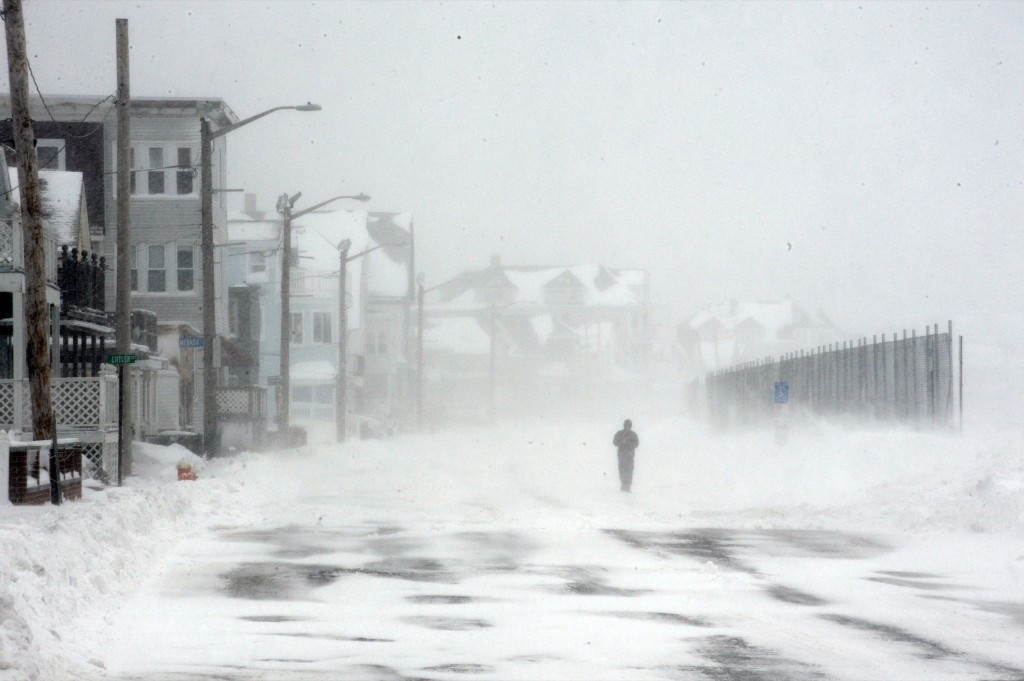 A man walks down a snowy street following an overnight blizzard in Winthrop, Mass. Darren McCollester/Getty Images
