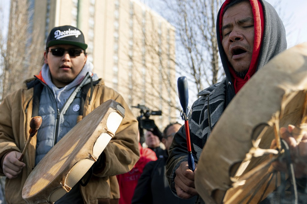 Sleepy Eye Lafromboise, right, and his son Eshtakaba, both of the Sioux Nation, sing during a gathering of Native American supporters in front of the Catholic Diocese in Covington, Ky., Tuesday, Jan. 22, 2019. (AP Photo/Bryan Woolston)