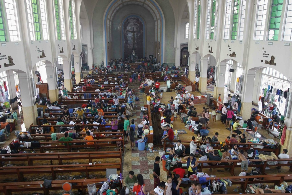 Residents seek refuge inside a Catholic church which has been converted into an evacuation center after super Typhoon Haiyan battered Tacloban. REUTERS/Romeo Ranoco