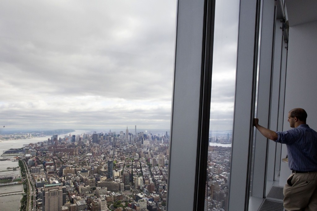 A visitor to One World Observatory looks over Manhattan, Wednesday, in New York. AP Photo/Mark Lennihan
