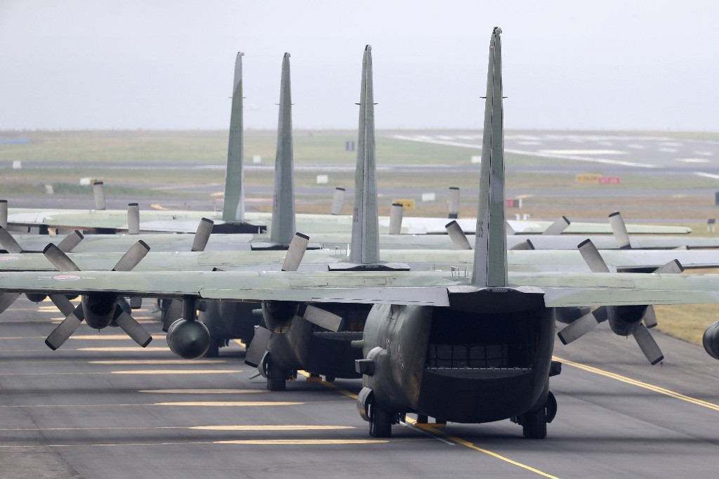 In this Nov. 11, 2018 photo, South Korea's Air Force cargo planes C-130 carrying boxes of tangerines, is seen before its take off for North Korea at the Jeju International Airport on Jeju Island, South Korea. South Korea has airlifted thousands of boxes of tangerines to North Korea in return for the North's large shipments of pine mushrooms in September.(Park Ji-ho/Yonhap via AP)