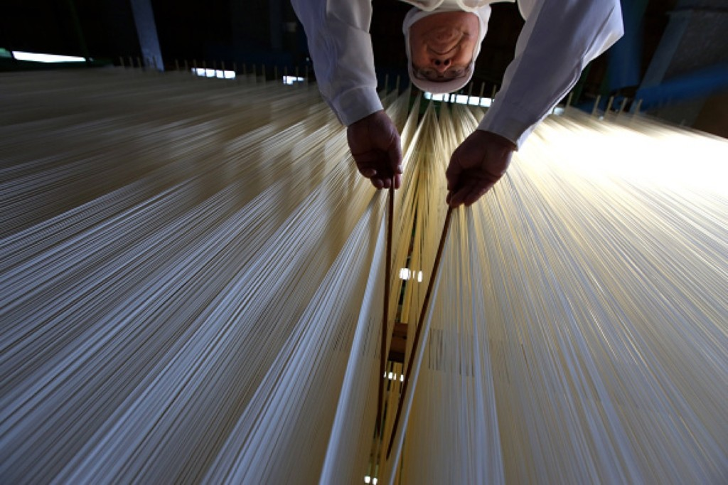 Japanese somen maker, Yoshinobu Izuhara, uses chopsticks to stretch drying Ibonoito somen noodles in Tatsuno, Japan. Buddhika Weerasinghe/Getty Images