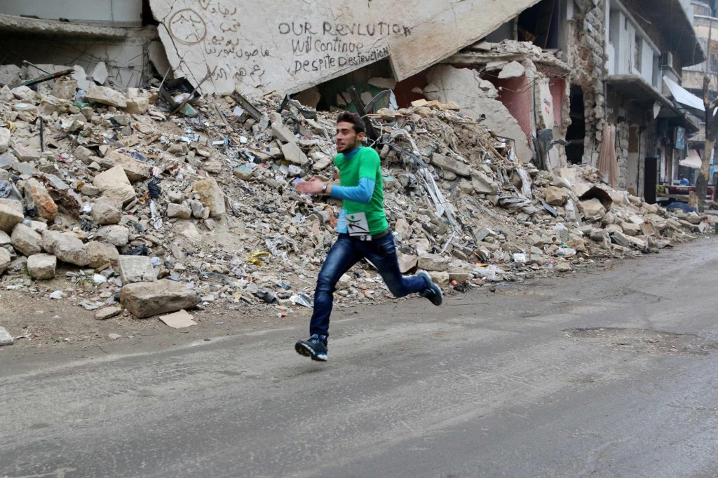 A participant in a race runs past a damaged building in Aleppo's Bustan al-Qasr neighborhood. REUTERS/Mahmoud Hebbo