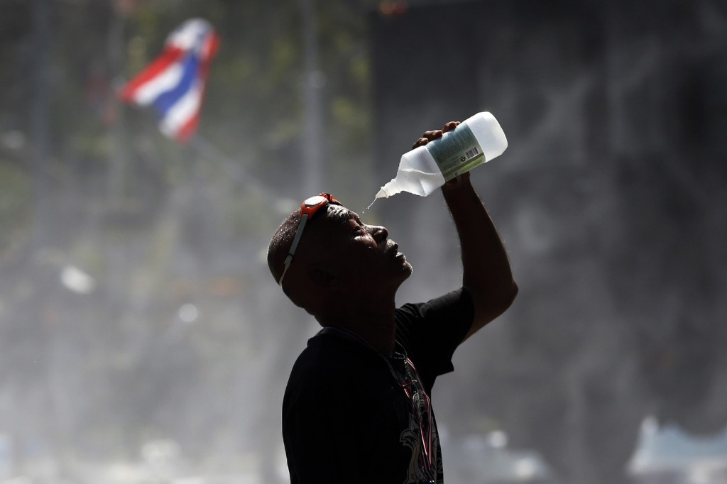 An anti-government protester recovers from teargas after clashes with police in front of the Government House in Bangkok, Monday. REUTERS/Damir Sagolj