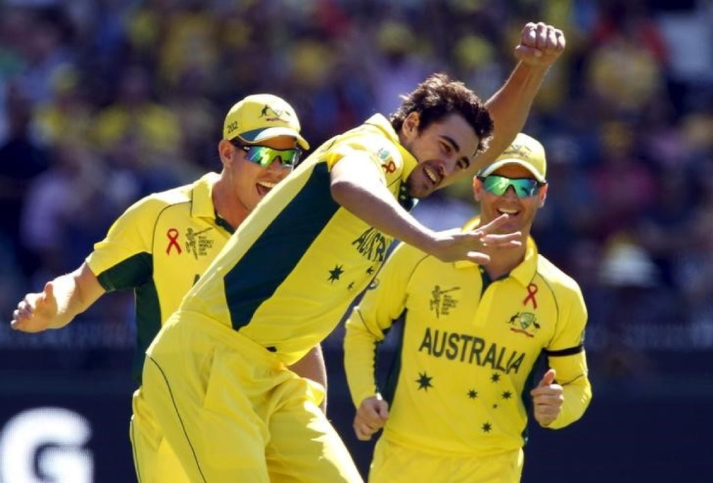 Australia's Mitchell Starc celebrates with teammates James Faulkner and captain Michael Clarke after bowling New Zealand's captain Brendon McCullum for a duck during their Cricket World Cup final match, in Melbourne, Sunday. REUTERS/Brandon Malone