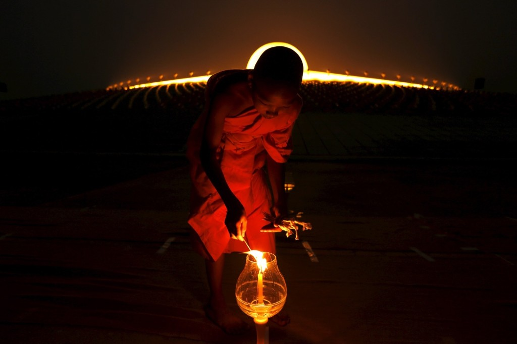A Buddhist monk lights a candle at Wat Phra Dhammakaya during a ceremony on Makha Bucha Day in Pathum Thani province, north of Bangkok. REUTERS/Jorge Silva