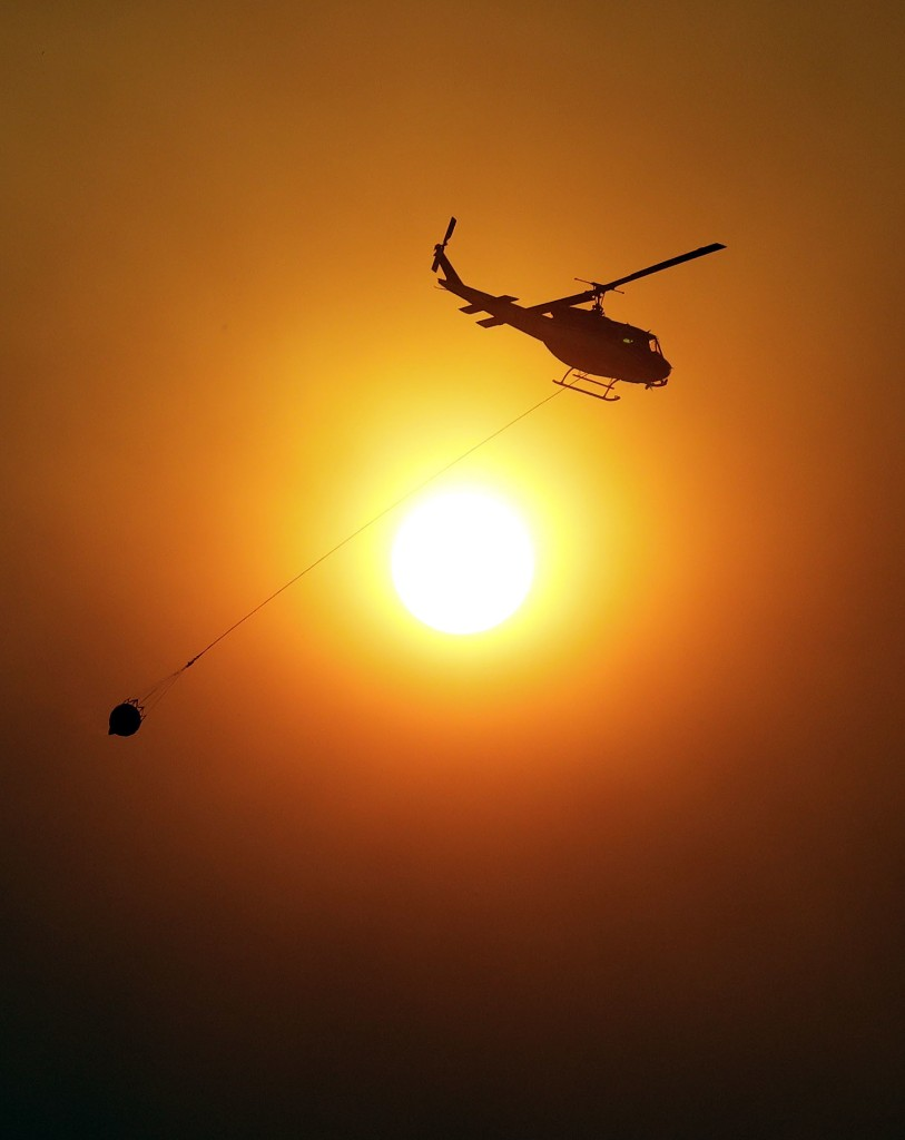 A helicopter carries water to drop on an advancing wildfire Monday, July 30, 2018, in Finley, Calif. Northern California fire officials have added residents of two towns near Clear Lake to the list of those ordered to evacuate. The notice was issued Monday for the towns of Kelseyville and Finley. (AP Photo/Marcio Jose Sanchez)