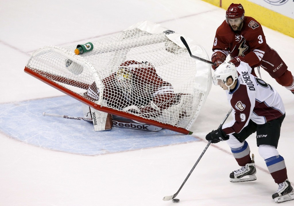 As Colorado Avalanche Matt Duchene moves to the net to shoot the puck, Arizona Coyotes goalie Mike Smith has the goal fall over on him. AP Photo/Ross D. Franklin