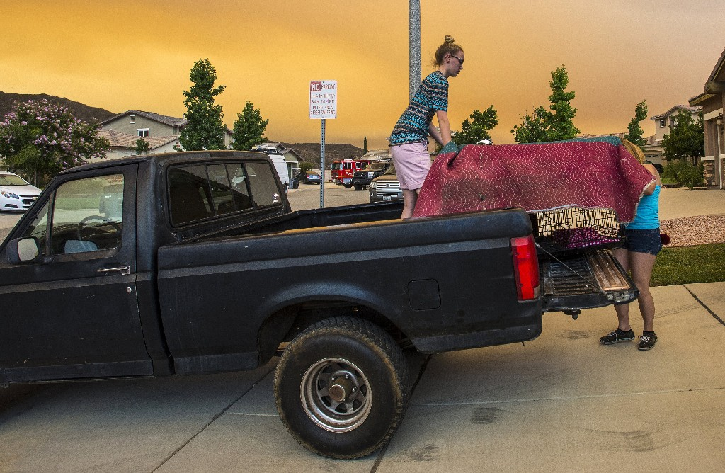Residents along Crystal Ridge Court in Lake Elsinore, Calif., load a truck as they evacuate as the Holy Fire burns near their home on Wednesday, Aug. 8, 2018. (Mark Rightmire/The Orange County Register via AP)