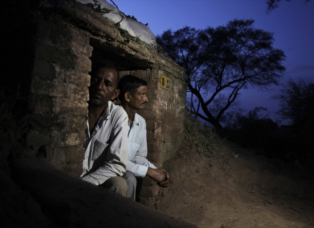 Indian villagers take shelter inside an army bunker anticipating firing from the Pakistan side of the border at Abdullian village in Ranbir Singh Pura. AP Photo/Channi Anand