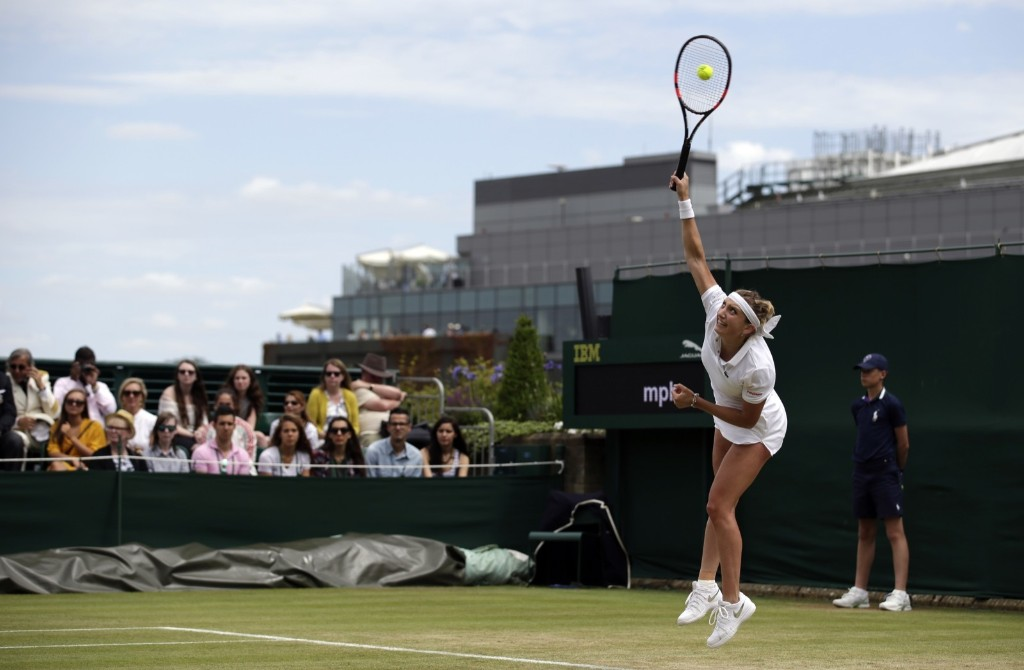 Timea Bacsinszky of Switzerland serves to Monica Niculescu. AP Photo/Pavel Golovkin