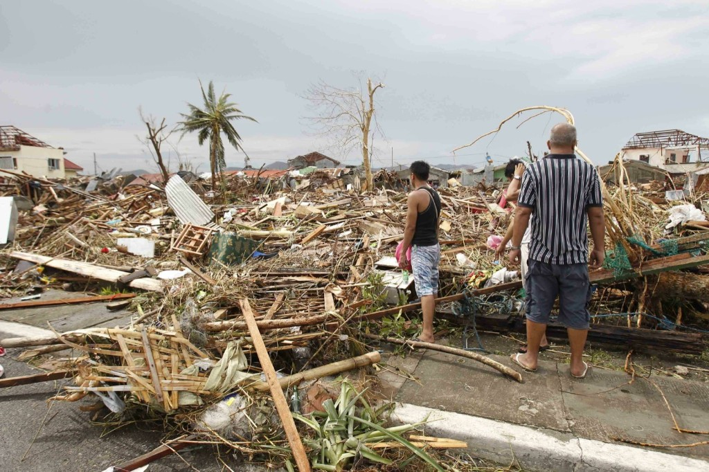Survivors assess the damage after super Typhoon Haiyan battered Tacloban city. REUTERS/Romeo Ranoco