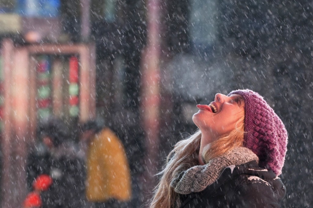 A tourist catches snowflakes on her tongue during snow fall in Times Square, Thursday. A major snowstorm producing blizzard-like conditions hammered the northeastern United States causing more than 1,000 flight delays and cancellations. REUTERS/Darren Ornitz