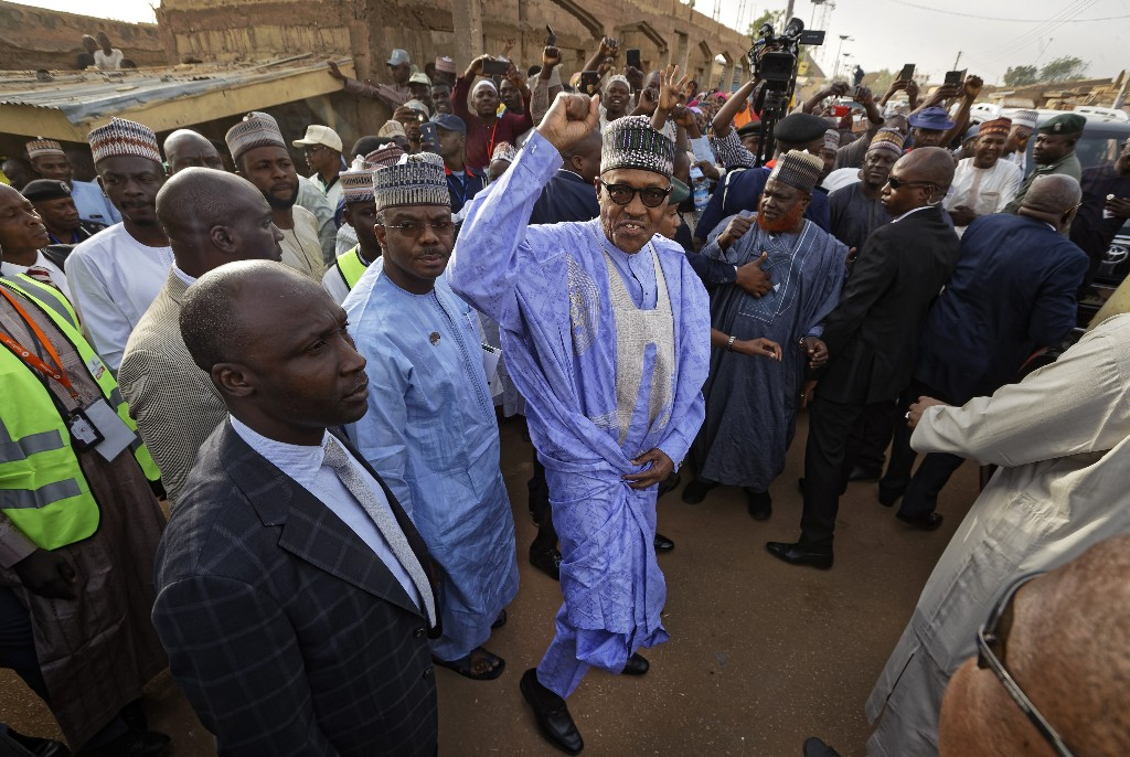 Nigeria's President Muhammadu Buhari gestures to supporters after casting his vote in his hometown of Daura, in northern Nigeria Saturday, Feb. 23, 2019. Nigerians are going to the polls for a presidential election Saturday, one week after a surprise delay for Africa's largest democracy. (AP Photo/Ben Curtis)