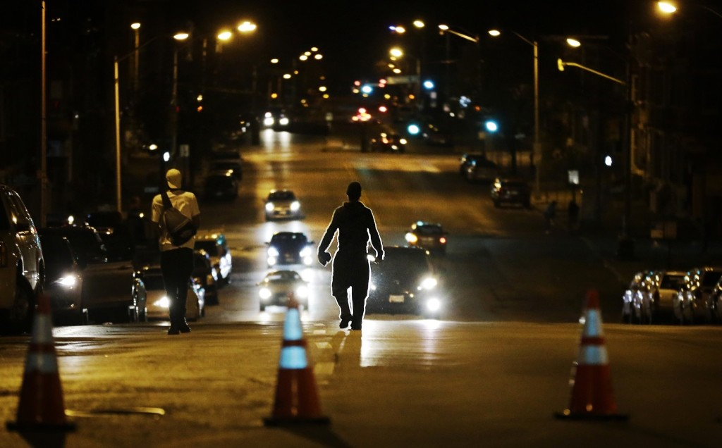 Youths walk away from police in riot gear after a 10 p.m. curfew went into effect Thursday in Baltimore. AP Photo/David Goldman