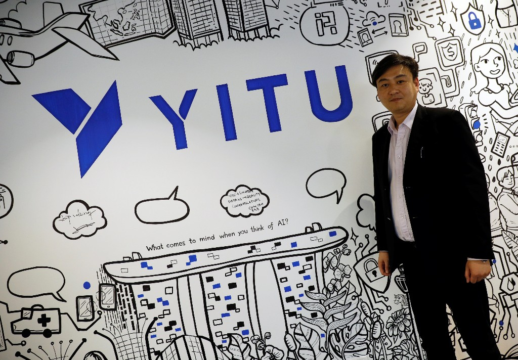 Yitu's Southeast Asia, Hong Kong and Macau General Manager Lance Wong poses with the company's signage in its office in Singapore April 10, 2018. Picture taken April 10, 2018. REUTERS/Edgar Su